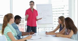 Man giving presentation of ideas to his colleagues at a meeting stock footage
