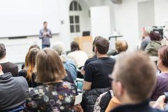Man giving presentation in lecture hall at university. Male speaker giving presentation in lecture hall at university workshop. Audience in conference hall Royalty Free Stock Photography