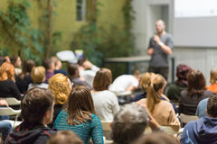 Man giving presentation in lecture hall at university. Royalty Free Stock Photography