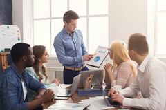 Man giving presentation to colleagues in office. Businessman giving presentation to colleagues in modern office. Young business team discussing new marketing Royalty Free Stock Image