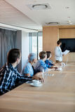 Man giving presentation to her colleagues in conference room Stock Photo