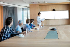 Man giving presentation to her colleagues in conference room Royalty Free Stock Photos