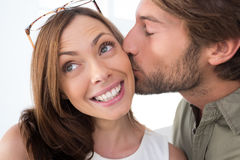 Man giving pretty woman kiss on the cheek Stock Image
