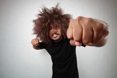 Man giving punch. Wide angle view of a man with funky hairstyle giving a punch Stock Photography