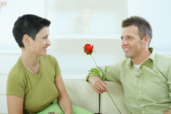 Man giving red rose. Young couple sitting on sofa at home. Man giving red rose to woman, smiling Stock Image