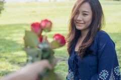 A man giving red rose flowers to asian girlfriend on Valentine`s day. With green grass background Stock Photo