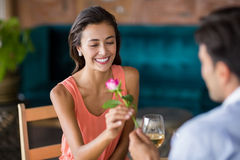 Man giving red rose to woman. Man giving red rose to women in restaurant Royalty Free Stock Photo