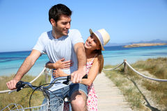Man giving ride to his girlfriend on bicycle. Man giving bike ride to girlfriend on beautiful Island Stock Images
