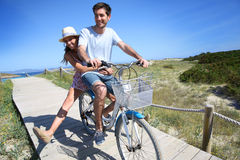 Man giving ride to his girlfriend on bicycle Stock Photo