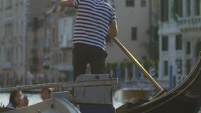 Man giving ride to tourists on gondola, propelling boat down channel with oar. Stock footage stock video