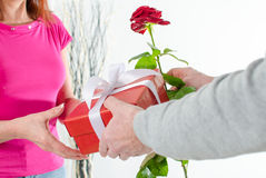 Man giving a rose and a gift to a woman Stock Photography