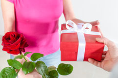 Man giving a rose and a gift to a woman Stock Images