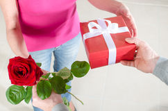 Man giving a rose and a gift to a woman Stock Image