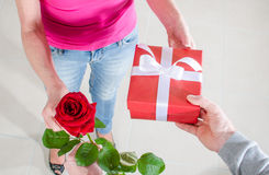 Man giving a rose and a gift to a woman Royalty Free Stock Photo
