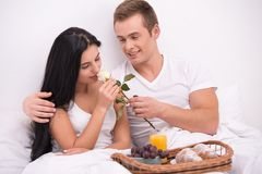 Man giving rose to his wife while having breakfast Stock Photography