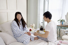 Man giving rose to woman in bed Royalty Free Stock Photo