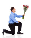 Man giving roses. Young man knee down on floor and giving bunch of roses isolated on white Royalty Free Stock Photo