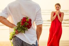 Man giving roses to his surprise and wonder woman on the ocean beach. romantic date or wedding or valentines day concept