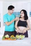 Man giving salad to pregnant woman Stock Image