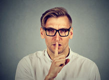 Man giving Shhhh quiet silence secret. Finger on lips gesture Stock Images