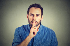 Man giving Shhhh quiet, silence, secret gesture stock photos
