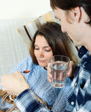 Man giving  sirup to unwell woman Stock Image