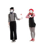 Man giving small red heart to amazed woman. Portrait of mimes. man giving small red heart to amazed woman. isolated on white background Stock Photo