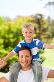 Man giving son a piggyback. In the park Royalty Free Stock Photo