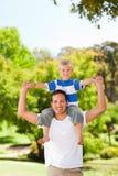 Man giving son a piggyback. In the park Royalty Free Stock Photos