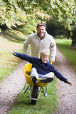 Man giving son ride in wheelbarrow Royalty Free Stock Images