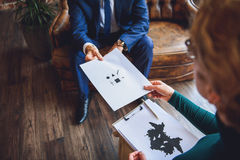 Man giving strange test to woman. Man in suit is sitting on couch. He transferring sheet to psychologist. She holding tablet Stock Images