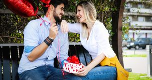 Man giving surprise gift as present to his lovely girlfriend. He is dating Stock Photography