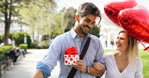 Man giving surprise gift as present to his lovely girlfriend. He is dating Royalty Free Stock Photos