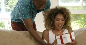 Man giving a surprise gift to his woman. In living room 4k stock video