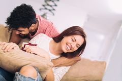 Man giving a surprise gift to woman. Man giving a surprise gift to women at home Stock Photography