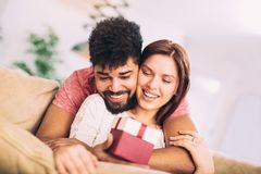 Man giving a surprise gift to woman. Man giving a surprise gift to women at home Royalty Free Stock Photos