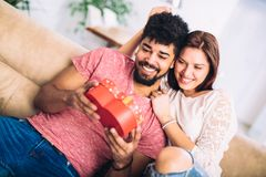 Man giving a surprise gift to woman. Man giving a surprise gift to women at home Stock Photos