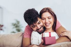 Man giving a surprise gift to woman. Man giving a surprise gift to women at home Stock Photo