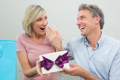Man giving a surprised woman a birthday gift Stock Images