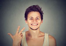 Man giving a three fingers sign gesture with hand. On gray background Royalty Free Stock Image