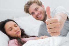 Man giving thumb up while his wife is sleeping Stock Images
