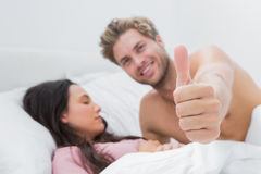 Man giving thumb up next to his sleeping wife Royalty Free Stock Images