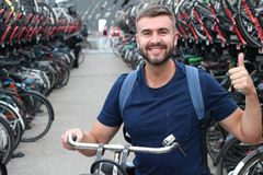 Man giving thumbs up in bicycle parking lot stock images