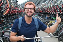 Man giving thumbs up at bicycle parking lot royalty free stock photos