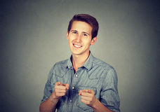 Man giving thumbs up pointing fingers at camera picking you. Portrait handsome young smiling man giving thumbs up pointing fingers at camera, picking you as Stock Photos