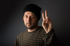 Man giving two fingers as peace or victory symbol Stock Photo