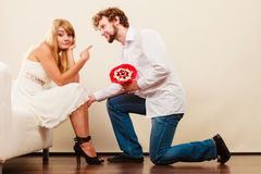 Man giving unhappy woman candy bunch flowers. Royalty Free Stock Photos