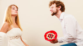 Man giving unhappy woman candy bunch flowers. Royalty Free Stock Photo