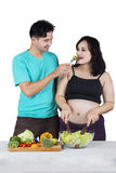 Man giving vegetable to his wife Royalty Free Stock Images