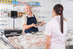 Man giving a white salmon to a costumer. Seller showing a fish to a costumer royalty free stock photo